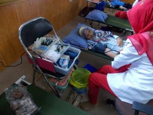 terlihat salah satu peserta donor darah (kiri) sedang dilakukan pengambilan darah oleh petugas Palang Merah Indonesia (PMI). Foto : Prabu
