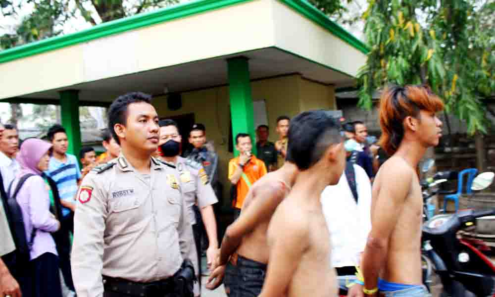 terlihat polisi sedang menggiring pelaku pembredelan mobil bus UIN Raden Fatah Palembang (11/9)  di kompleks UIN Raden Fatah. Foto : Jeo