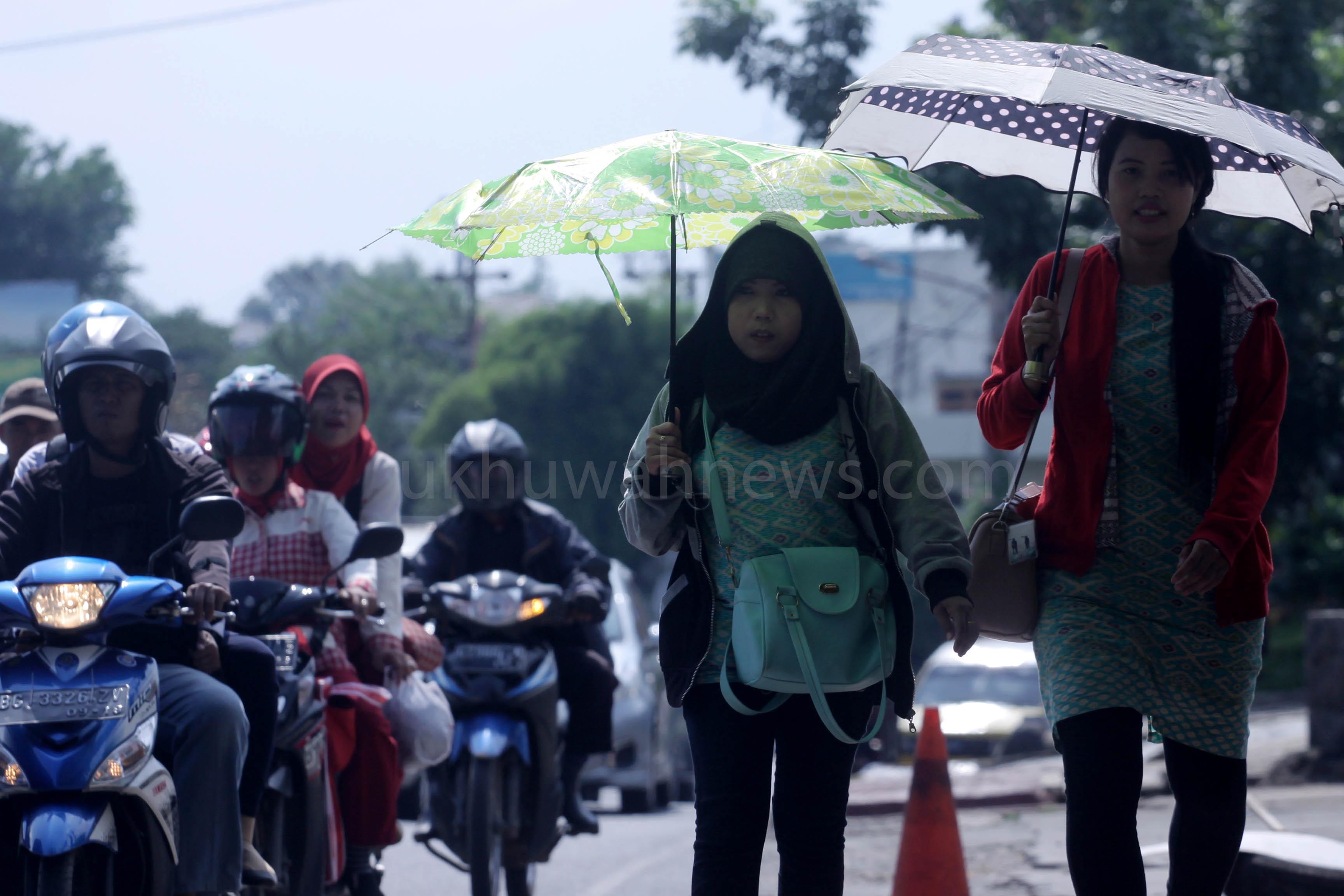 Dua orang warga menggunakan payung saat terik matahari di jalan Merdeka, Palembang, Senin (21/3/2016). Cuaca panas yang melanda beberapa kota di Indonesia, hal ini terjadi ketika matahari melalui garis katulistiwa yang disebut dengan fenomena Aquinox, dengan suhu mencapai 40 derajat celcius dan dapat menimbulkan polusi udara sehingga meningkatnya intensitas debu di jalanan, sehingga warga rentan terkena radang tenggorokan. Ukhwuahnews.com/HairulAkbar
