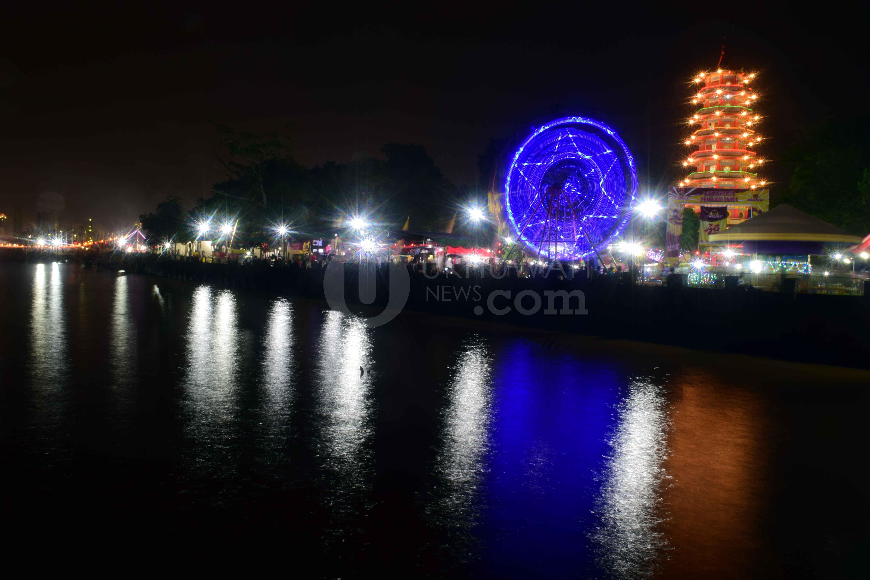 Suasana malam hari saat perayaan Cap Go Meh di Pulau Kemaro Kota Palembang, (8/2/2017). Selain dipenuhi oleh etnis Konghucu  yang ingin beribadah, perayaan Cap Go Meh juga dipenuhi oleh wisatawan lokal yang ingin sekedar menikmati jajanan yang disediakan oleh penjual. Dalam perayaan ini juga menyediakan permainan-permainan sederhana seperti roda berputar, komedi putar dan sebagainya.