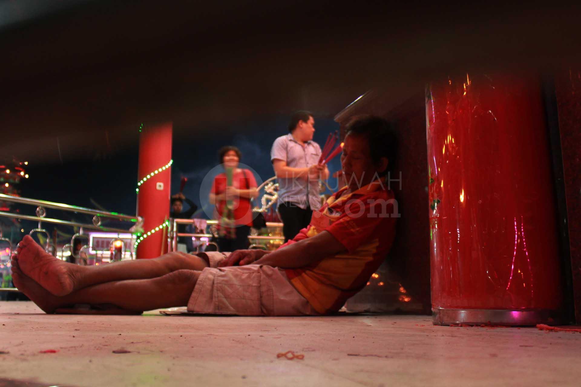 Salah satu petugas Perayaan Cap Go Meh tertidur saat malam perayaan sedang berlangsung di Pulau Kemaro Kota Palembang, (9/2/2017). Para petugas perayaan Cap Go Meh harus bekerja selama 24 jam full guna melayani para masyarakat yang ingin beribadah.