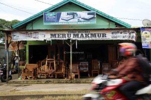 Seorang pengendara motor melewati tempat penjualan karya ukir kayu di daeraj Sukabangun, Palembang