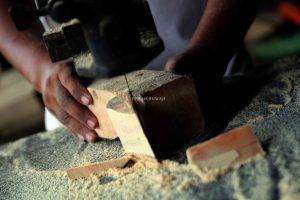 Seorang pekerja sedang mengerjakan proses Pembentukan awal balok kayu menjadi sebuah ukiran