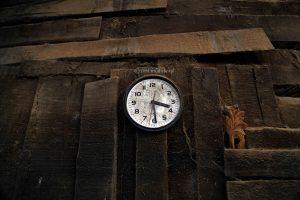 Jam dinding yang tertutup oleh debu sisa serutan kayu
