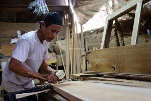 Seorang pekerja sedang mengukur panjang media kayu yang akan digunakan sebagai pondasi pembuatan lemari kayu