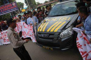 Mobil polisi menembus barisan demonstran yang tergabung dalam Gerakan Mahasiswa di depan halaman kantor Rektorat UIN Raden Fatah Palembang, (30/4/2018). GAM diantaranya menuntut penjelasan mengenai sistrm Uang Kuliah Tunggal (UKT) dan menagih janji pembangunan kampus B UIN RF yang tak kunjung direalisasikan.