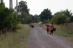 Dua anak kecil bersiap untuk pergi memancing di kawasan UPT 2 Desa Sungai Rambutan.