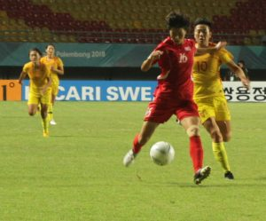 Pesepak bola wanita Korea Utara Kim Un Ha ( kiri) mengoper bola kepada kawan se-timnya yang sambil di bayangi oleh pemain China  Li ying (kanan) pada babak penyisihan grup B sepak bola wanita Asian Games 2018 di Stadion Gelora Sriwijaya Jakabaring, Palembang, Sumatera Selatan. Rabu (22/8). China menang atas PRK korea utara dengan skor 2-0. Ukhuwahfoto/M. Amin Qoblal Fajri