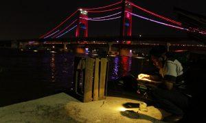 Malam hari, warga biasa mancing ikan dan udang di dermaga berlatar Jembatan Ampera dan jalur rel LRT. Sukardi (38), tengah mencari peruntungannya mencari ikan di Sungai Musi. Foto: Nopri Ismi
